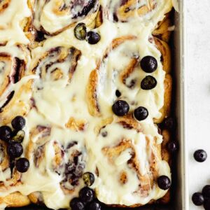 baking pan with cinnamon rolls, fresh blueberries, and cream cheese frosting