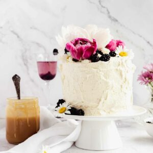 decorated cake with peonies and blackberries