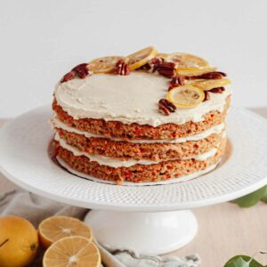 triple layer vegan carrot cake with candied lemons and pecans on top